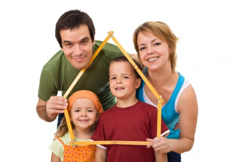 Happy family with their kids - real estate concept  Visiting Your Home Under Construction Family house e1387383766206